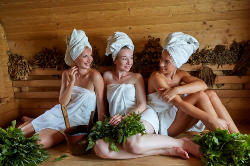 three beautiful young women in towels realxing in wooden sauna. inside shot with natural light.