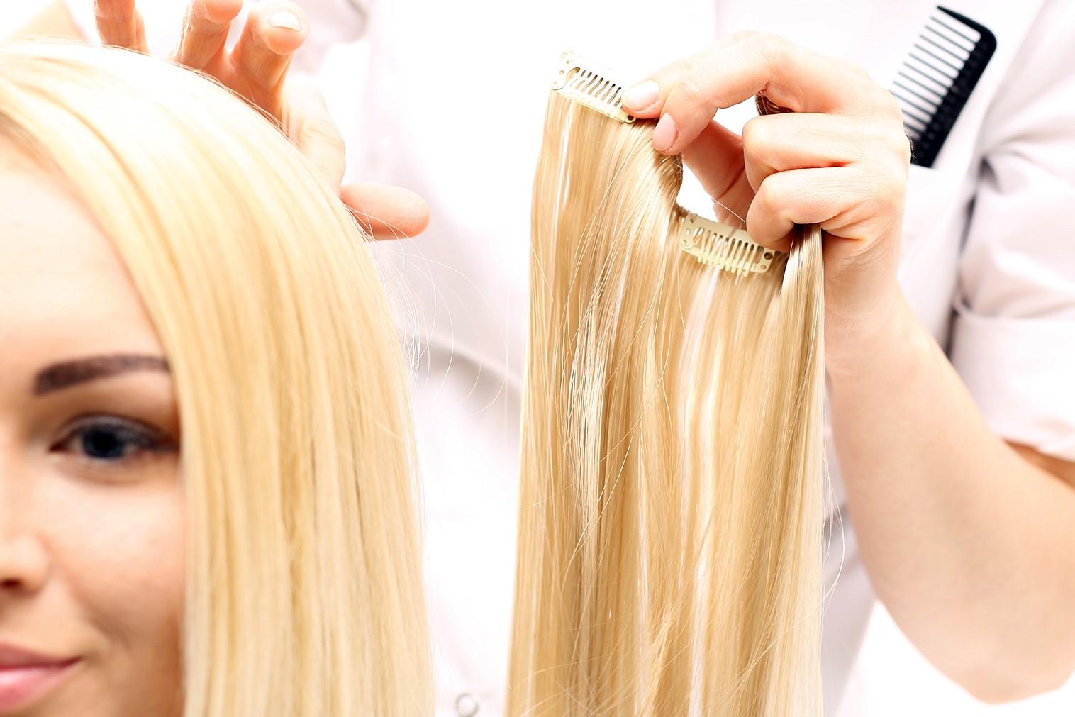 Zagęszczanie włosów.Fryzjer przedłuża włosy dopinając pasma włosów