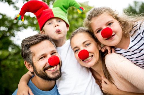 Glückliche Familie hat Spaß im Karneval in Verkleidung mit roten Nasen
