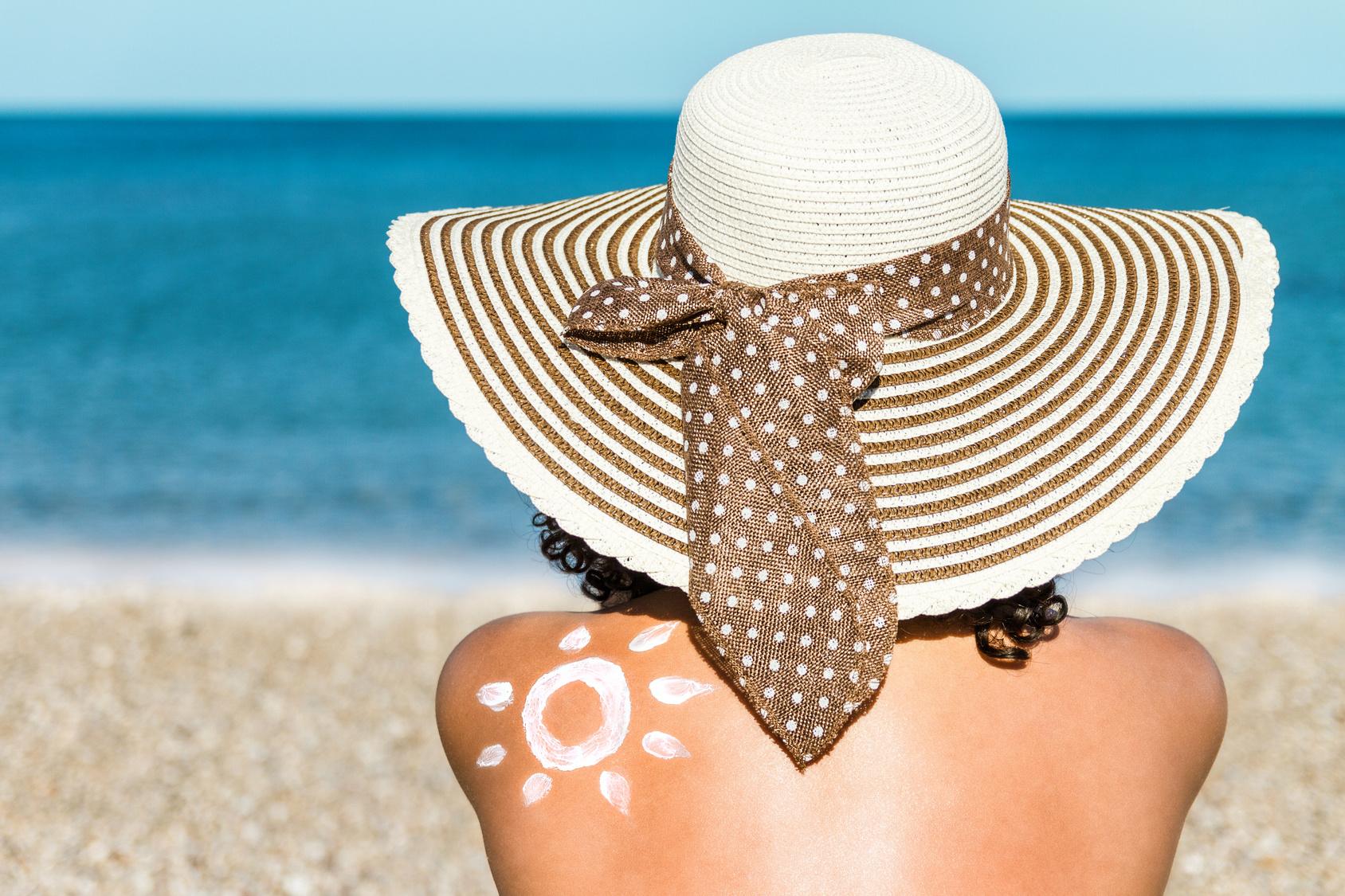 Frau mit Sonnenhut am Meer