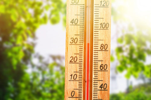 Thermometer displaying high 30 degree hot temperatures in sun summer day