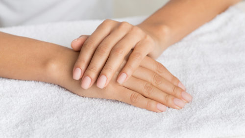 Hand care. Woman getting manicure procedure in spa salon, panorama