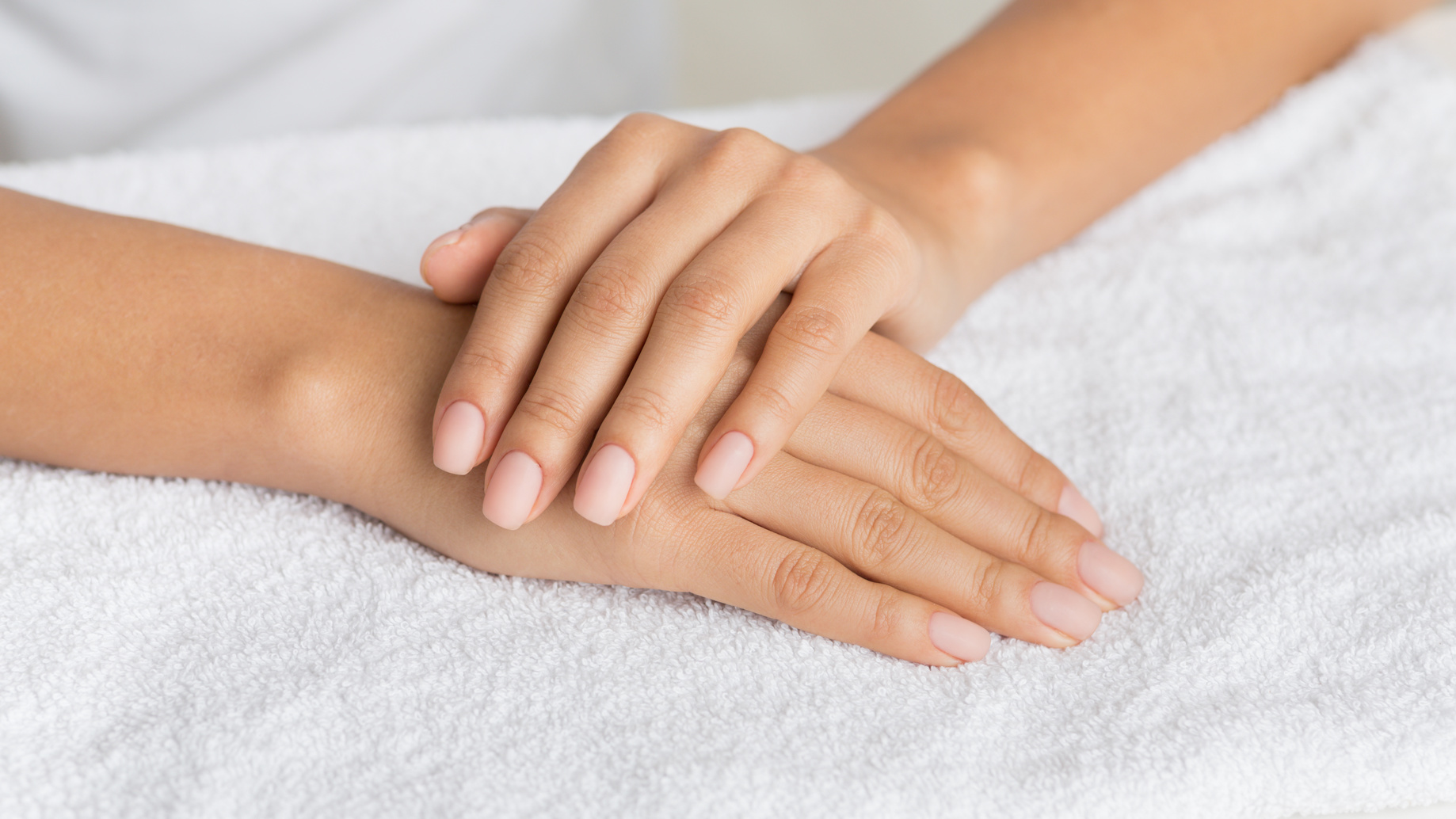 Hand care. Woman getting manicure procedure in spa salon, panorama