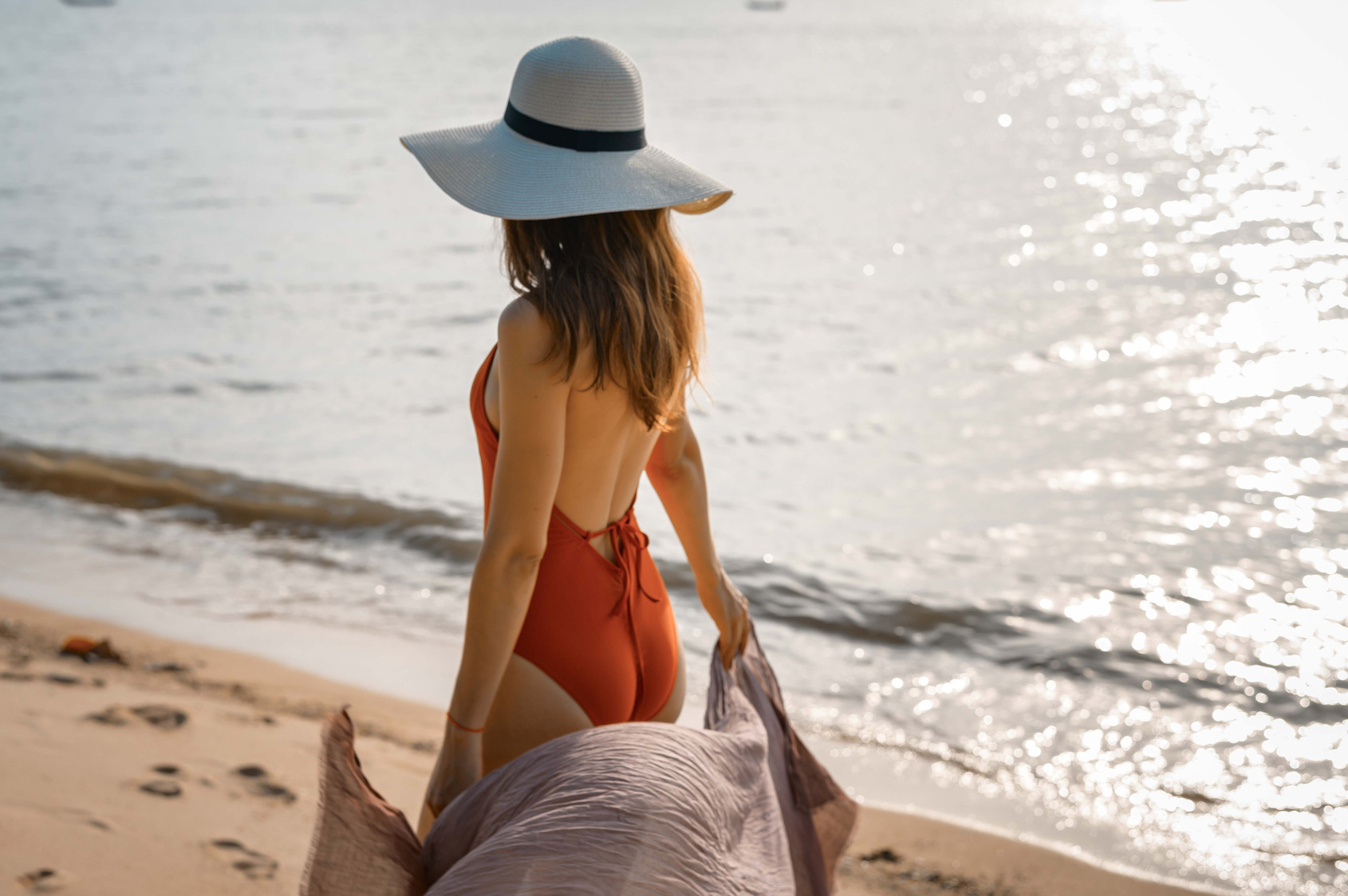 Beautiful woman with red swimsuit on the beach in Summer
