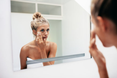 Reflection of a female in mirror rubbing cosmetic cream on her face. Female putting on moisturizer on her facial skin in bathroom.