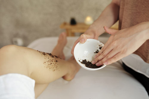 Close-up image of cosmetologist applying natural apricot scrub on legs of young woman relaxing in spa salon