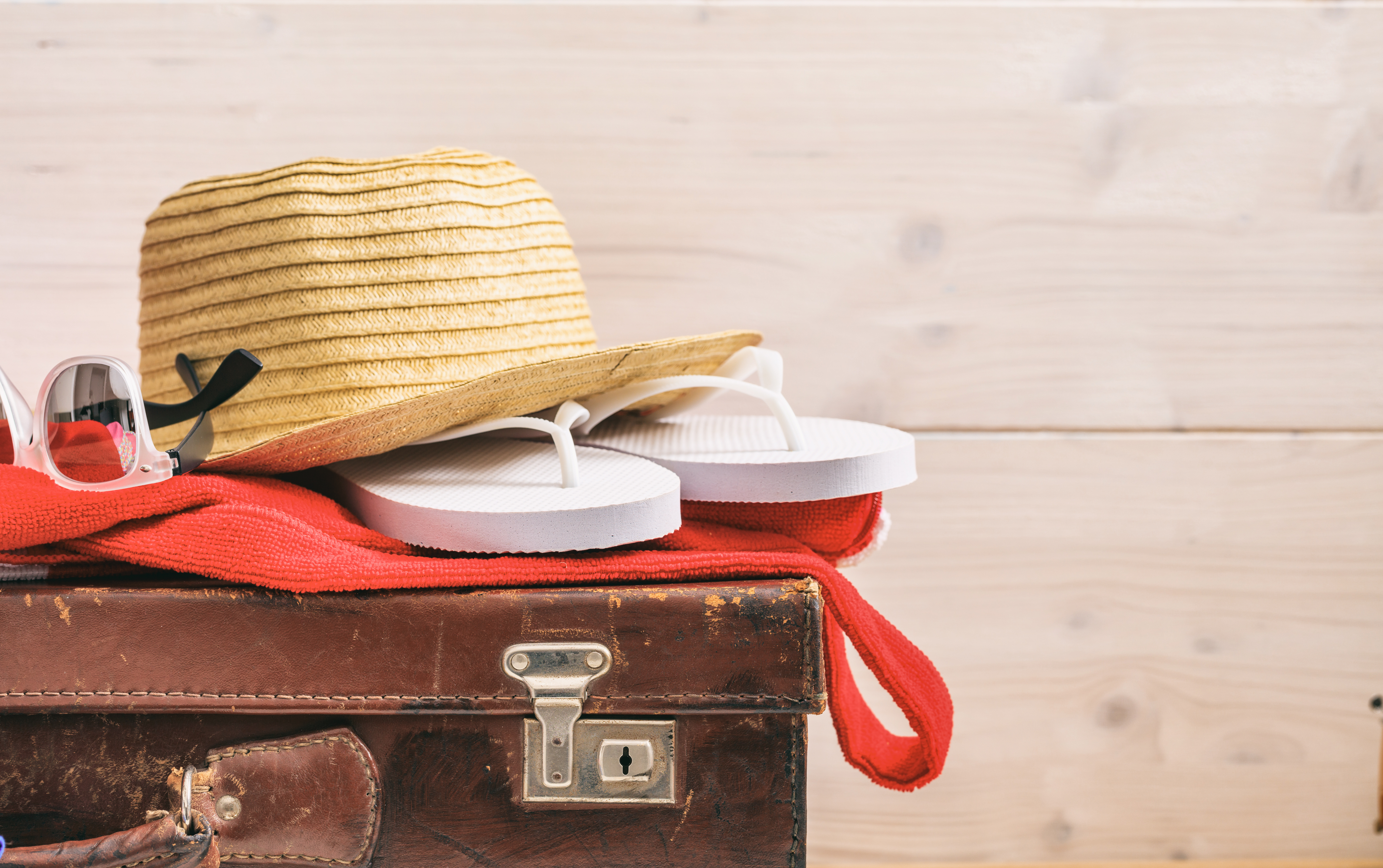 Beach accessories on an old suitcase - white wooden background - copy space