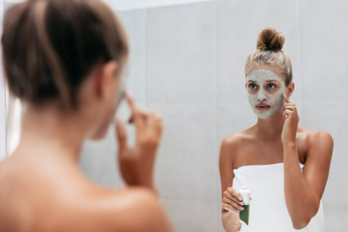 Beautiful young woman in bathroom applying mask on face looking at mirror. Girl taking care of her skin. Beauty treatment in bathroom.