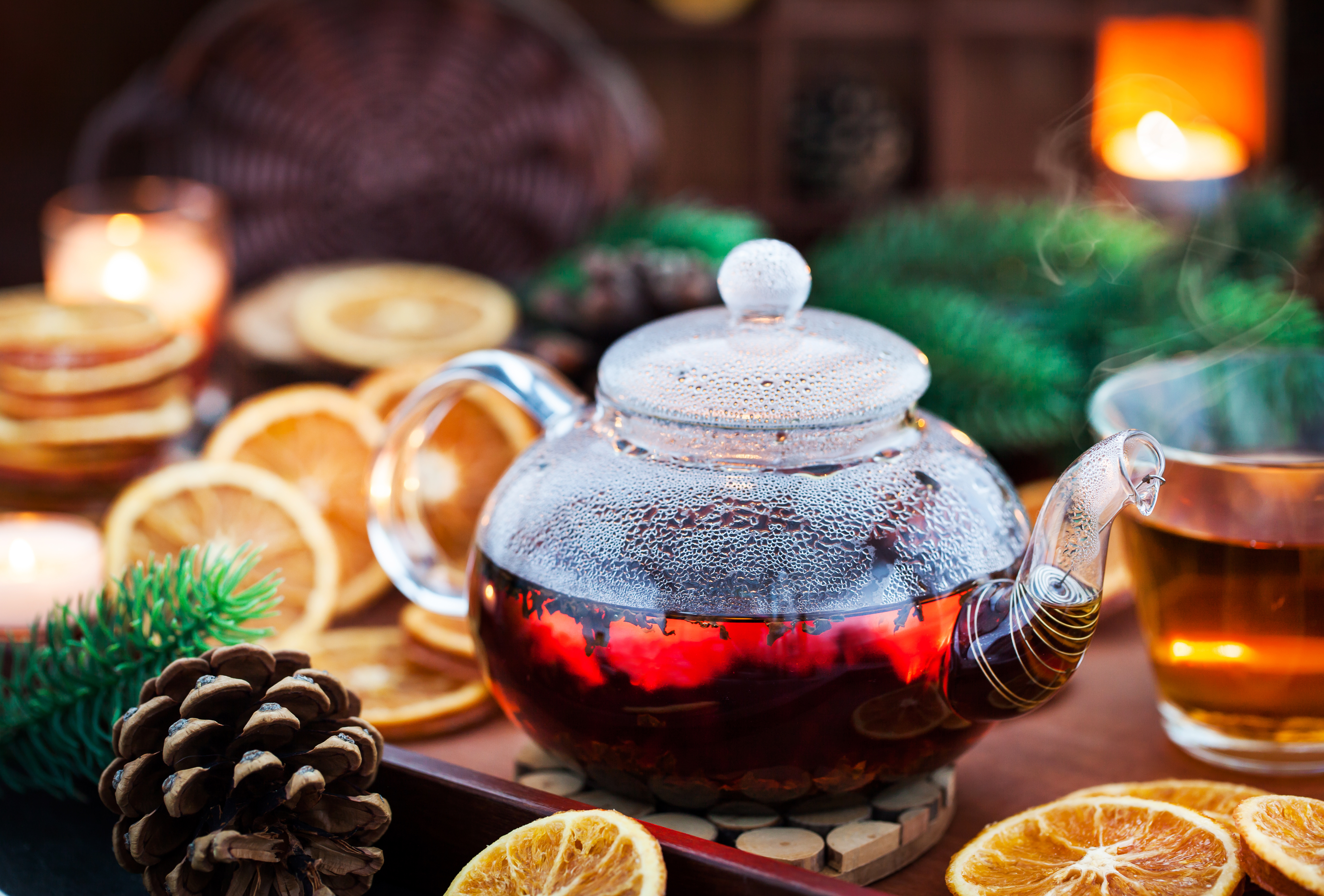 Glass teapot of hot black tea on cozy background with dried oranges and candles