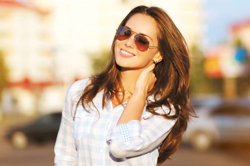 Fashion lifestyle portrait pretty woman in the sunglasses posing in the city summer, evening sunset sunny light, street fashion